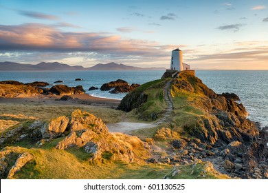 Sunset at Ynys Llanddwyn island on the coast of Anglesey in North Wales with the mountains of Snowdonia in the distance.
