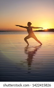 Sunset  yoga in shallow water near the ocean