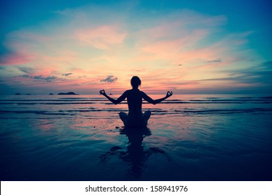 Sunset yoga woman on sea coast (in cold colors)