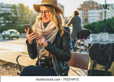 Sunset. Young woman tourist with backpack and camera, dressed in hat and glasses, sits on bench in city street and uses smartphone. Hipster girl chatting, blogging. Vacation, travel, social networks.
