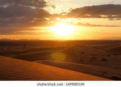 sunset/sunrise in the Sahara desert in morroco in Africa with people and footprints