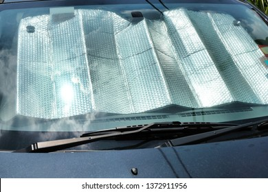 A sunshade shields a car's interior against the heat as the intensity of the midday sun is reflected on the windscreen.