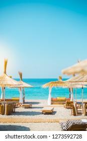 Sunshade umbrellas and deckchairs on the beautiful beach in Himara, turquoise water of Ionian Sea in Albania.