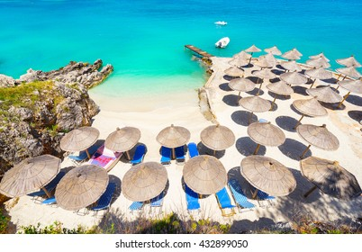 Sunshade umbrellas and deckchairs on the small beautiful Ksamil beach, Albania.