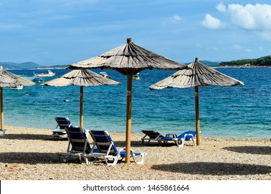 Sunshades and chairs on turquoise adriatic beach.