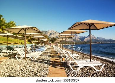 Sunshades and chaise lounges on beach. Turkey, Kemer. Beautiful view of mountains and sea.