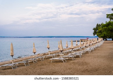 Sunshades and deck chairs on the empty beach of Crikvenica in the early morning. Crikvenica is a popular holiday resort in Kvarner riviera in Croatia