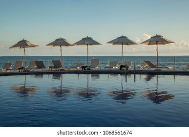 sunshades and lounges at poolside with ocean in the bachground