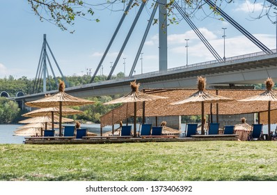 Sunshades or parasols on the Strand city beach in Novi Sad, Serbia with bridge and blue sky above ready for swimming summer season and vacation