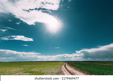 Sunshine Above Spring Rural Meadow Field And Country Open Road. Countryside Landscape With Path Way Under Scenic Summe Sky Before Rain. Sun Over Skyline Or Horizon.