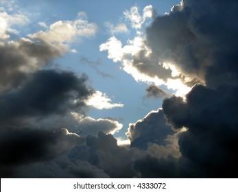Sunshine behind dark clouds on a summer day