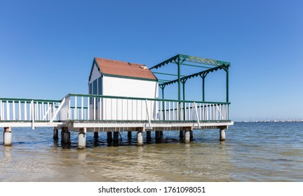 Sunshine and blue sky in the Mar Menor in eastern Spain. A small white pier with a wooden house also serves as a jetty for small boats.