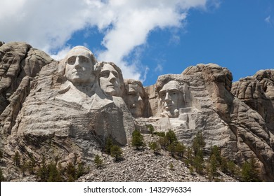 Sunshine, blue sky and white clouds provide a striking back drop for the carved faces of four famous United States Presidents in Mount Rushmore National Memorial.