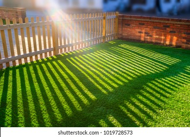 sunshine creating lens flare through a wooden picket fence in a front yard, front garden with artifical grass as a lawn and a red brick perimeter wall.