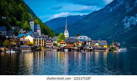 Sunshine evening scenery of beautiful Hallstatt at the wide lake on the background of rocky forested mountains