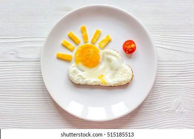 petit-déjeuner d'oeufs au plat au soleil pour enfant sur fond bois