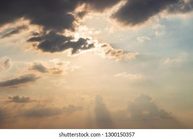 Sunshine hidden behind dark clouds in the sky before sunset