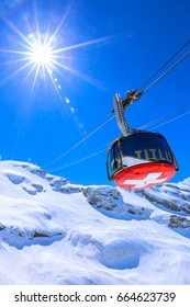 Sunshine over cable car to Mount Titlis in Swiss Alp covered with snow during winter, Switzerland