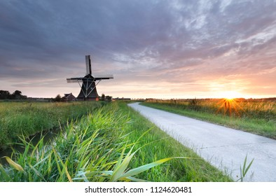sunshine over countryside road and windmill, Holland