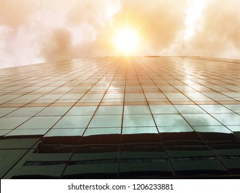 Sunshine over skyscraper with glass reflection and cloudy sky in hottest day.