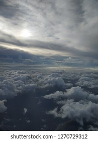 Sunshine peeking through clouds in low atmosphere against long horizon with multiple haphazard formations over ocean during daybreak