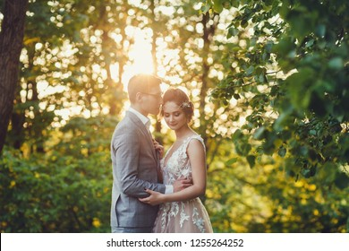 Sunshine portrait of happy bride and groom outdoor in nature location at sunset.