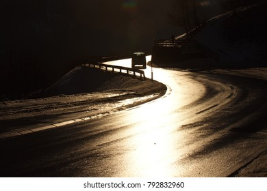 Sunshine reflections on the road in Alps with leading lines to a car silhouette on the horizon