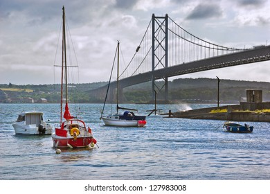 Sunshine sparkles on the sea under the dramatic arches of the Forth Road Bridge in North Queensferry, Scotland. Pleasure boats lie at anchor close to the shore as a wave breaks over the harbor wall.