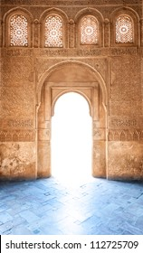 Sunshine through door to Granada palace. Sunlight on blue floor. Stone wall and windows in arabesque design. Ornate pattern of building in arabic style. Famous tourist destination in Spain, Europe.