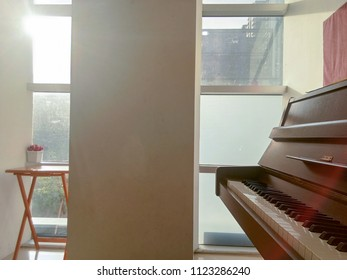 Sunshine through the window in the music, wooden table and fake flower in the pot on the corner and brown piano upright in white room