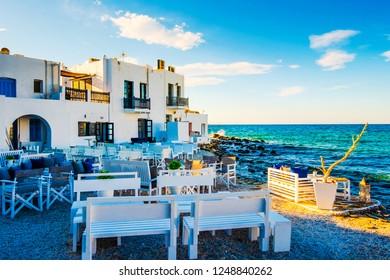 Sunshine view of white restaurant on turquoise stony bay of greek island Paros