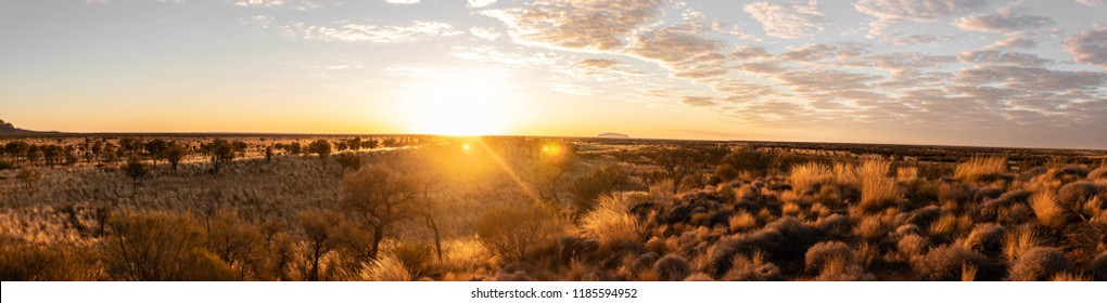 Sunsrise at Ayers Rock with clouds clearing up and the landscapecoming to life