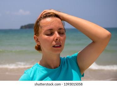 Sunstroke by tropical seaside. Health problem on vacation. Medicine on vacation. Dangerous sun. Beach day. Sunstroke on hot beach. Girl under sun. Unhealthy girl on beach by sea. Holiday health care