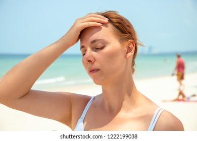 Sunstroke woman on sunny beach. Woman with headache. Hot sun danger. Health problem on holiday. Medicine on vacation. Dangerous sun. Beach life. Sunstroke on sunny beach. Healthcare in tropics