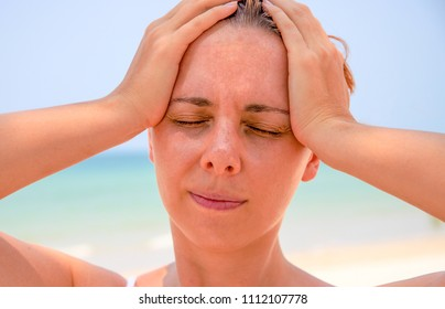 Sunstroke woman on tropical beach. Woman on hot beach with sunstroke. Headache from sun. Medicine on vacation. Dangerous sun. Beach life. Sunstroke on sunny beach. Healthcare in tropics