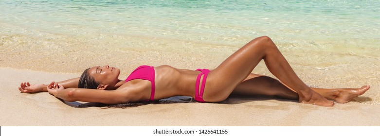 Suntan beach bikini woman lying down on sand relaxing sunbathing panoramic banner. Summer travel lifestyle swimsuit model tanning with sun tanned skin.