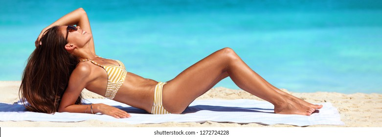 Suntan bikini woman sun tanning on beach - Asian sexy body model lying down on beach towel on perfect blue ocean water background banner panorama.