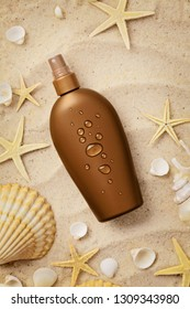 suntan cream bottle and seashells on sand beach