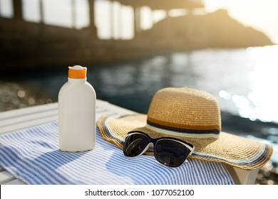 Suntan cream bottle and sunglasses on beach towel with sea shore on background. Sunscreen on deck chair outdoors on sunrise or sunset. Skin care and protection concept. Golden tan.