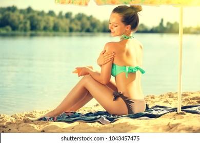 Suntan Lotion. Beauty young Woman Applying Sunscreen Solar Cream. Beautiful happy cute Girl applying Sun Tan Cream on her skin on the beach. Sun Tanning. Skin care and Protection. Vacation