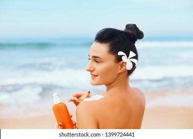Suntan Lotion. Sexy Young Woman in Bikini  Applying Sunscreen Solar Cream.Sun Protection. Sun Cream. Skin and Body Care.Girl Holding Moisturizing Sunblock. Sun shape on the shoulder. Skin Protection