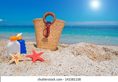 suntan lotion and straw bag at the beach
