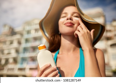 Suntan lotion. Woman applying sunscreen solar cream on face. Beautiful happy cute girl puts suntan cream from plastic container bottle on her nose and cheecks. Female in straw hat and bikini on beach.