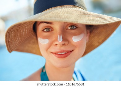 Suntan Lotion Woman Applying Sunscreen. Female smear  sun cream  on face. SkinCare.