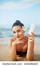Suntan lotion woman applying sunscreen solar cream. Beautiful happy cute woman  applying suntan cream from a plastic container to her nose with ocean in background.