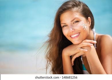 Suntan Lotion Woman Applying Sunscreen Solar Cream. Beautiful happy cute Girl applying Sun Tan Cream on her Face with ocean in background. Sun Tanning. Skin Protection