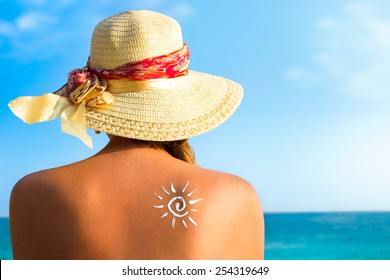 Suntan lotion woman with sunscreen solar cream over ocean background