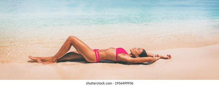 Suntan panoramic sexy bikini body Asian woman lying down on beach sand vacation banner. sun tan swimwear model panoramic horizontal crop of exotic holiday.