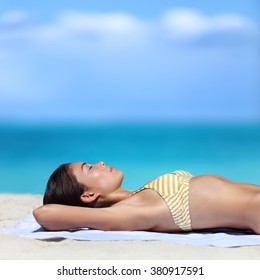 Suntan woman sunbathing sleeping on summer beach vacation. Sexy yellow stripes bikini girl lying down on white sand dreaming with sky copy space for summer travel  concept.