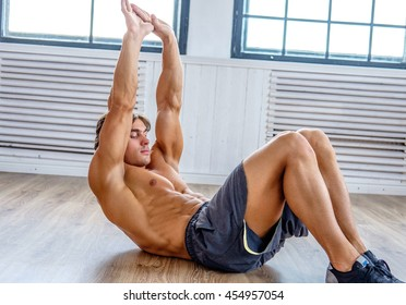 Suntanned athletic male doing stomach workouts on the floor in natural soft light.